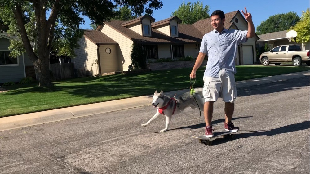 Efrain skating with Leo the husky